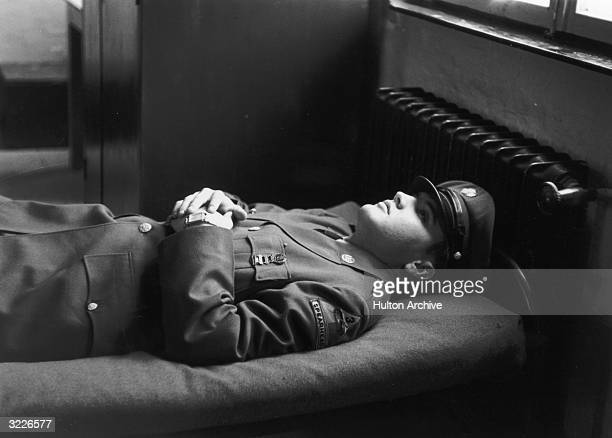 Portrait of American rock singer Elvis Presley , wearing a military uniform, lying on an army cot with his hands folded across his chest.