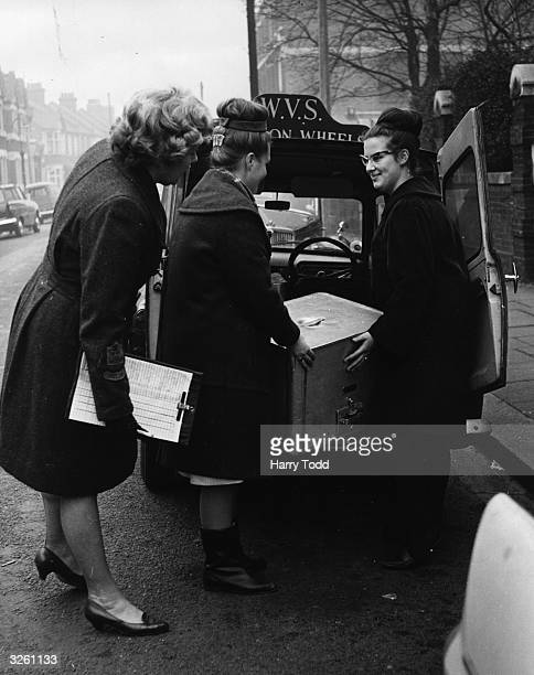 Florence Braybrook a Women's Voluntary Service organiser watches as two schoolgirls load a van with hot meals to take out to pensioners in East London