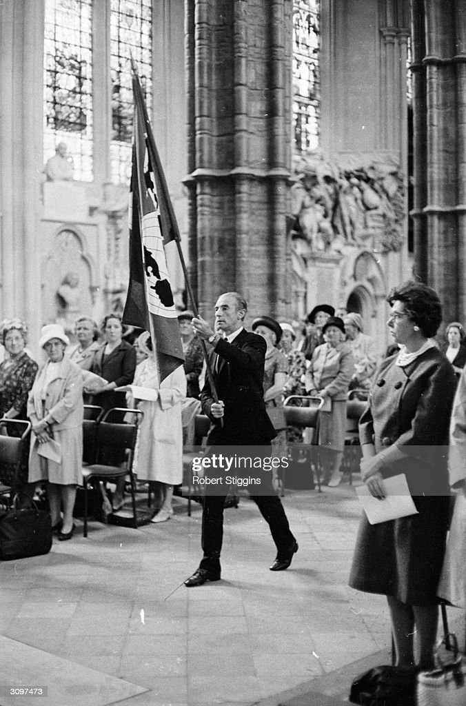 English footballer Sir Stanley Matthews (1915 - 2000) carries the FIFA flag into Westminster Abbey, where a service is being dedicated to the Worldwide Fellowship of Sport.