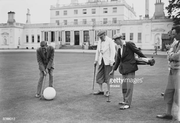 Members of the Fleetway House Golfing Society with a giant golf ball on the putting green on the club's annual day meeting at Stoke Poges in...