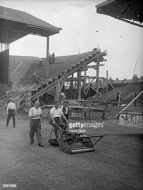 A groundsman mowing the pitch as a new grandstand is erected at Brentford Football Club London