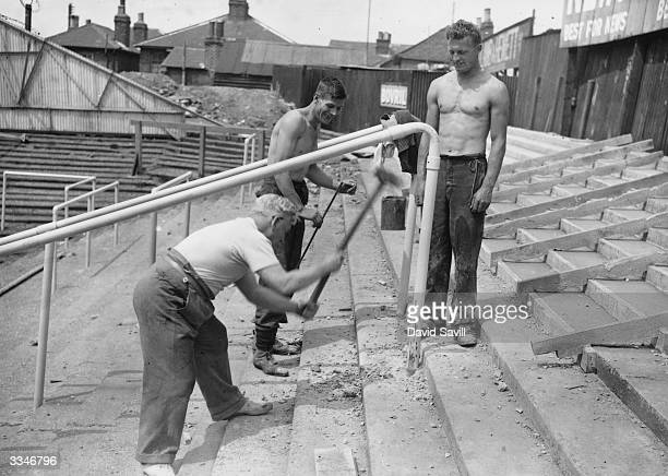 Brentford Football club's trainer helping two of the club's footballers to erect crush barriers on one of the new grandstands at their grounds in...