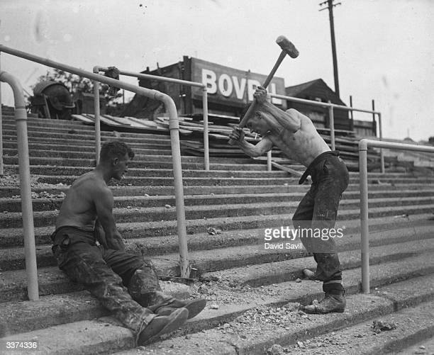 Nichols a goalkeeper at Brentford FC swings a 14lb hammer while teammate C Welsh holds a wedge They are helping to erect new crush barriers at their...