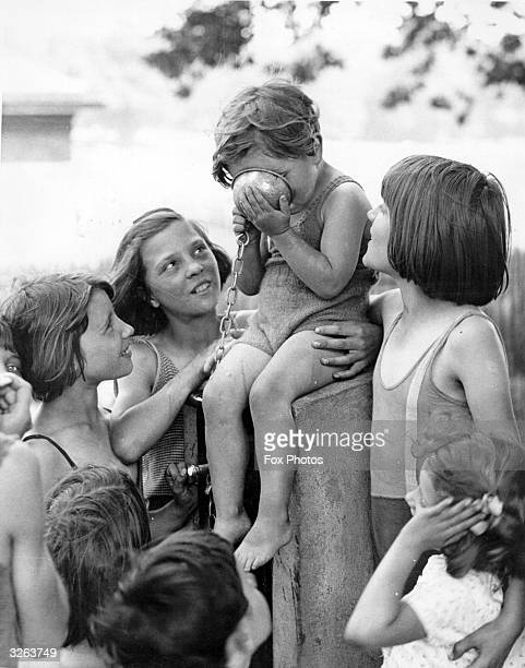 Youngsters gathered round the drinking fountain near the lido in Hyde Park wait patiently while the youngest member of the party takes his turn and...