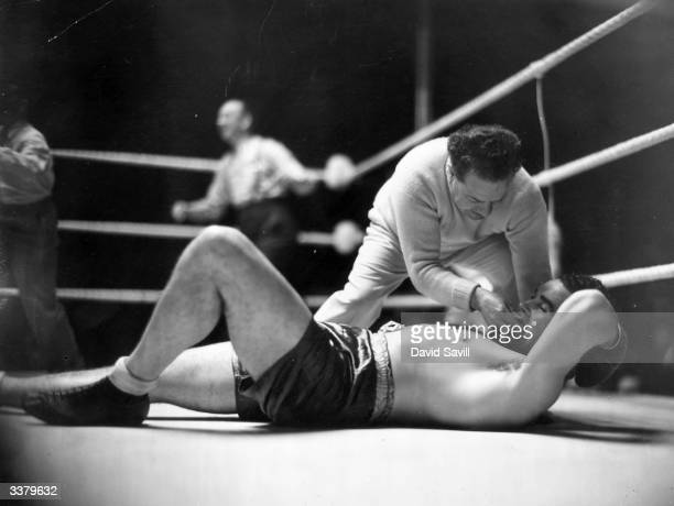 British heavyweight boxer Jack Doyle receives first aid after being knocked out by Eddie Phillips