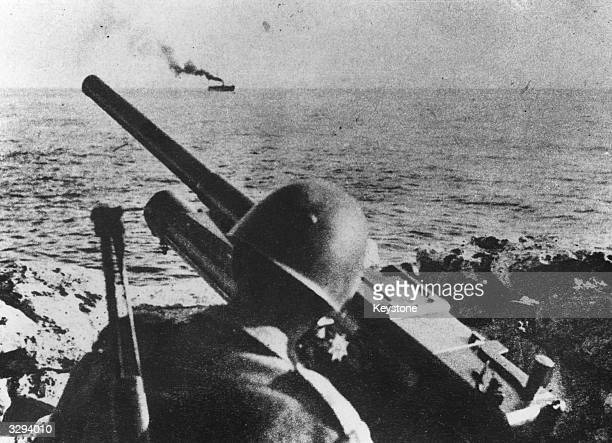 An Italian soldier manning a gun post on Sicily overlooking the sea.