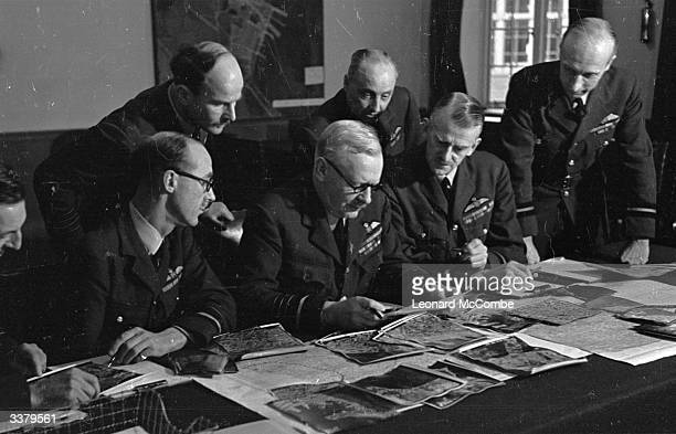 British Air Force officer Sir Arthur 'Bomber' Harris, commander-in-chief of RAF Bomber Command, studies documents in the bunker at Bomber Command...
