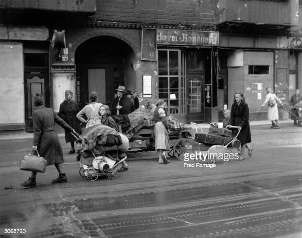 Evacuees return to Berlin after World War II to find their homes destroyed All their belongings are towed behind them in handcarts and prams