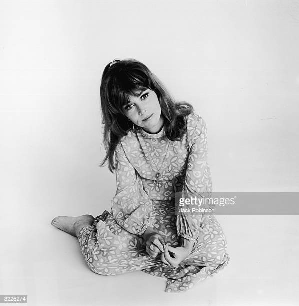 Fulllength studio portrait of American actor Lee Grant sitting on the floor wearing a flowerpatterned dress with a light backdrop