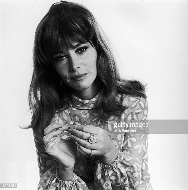 Studio portrait of American actor Lee Grant, wearing a flower-patterned dress and touching her fingertips, in front of a light backdrop,