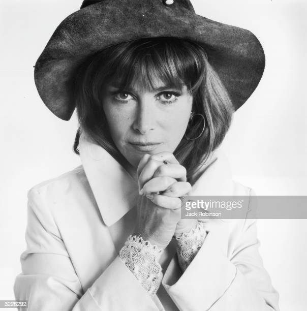 Studio portrait of American actor Lee Grant with her hands clasped wearing a suede hat and a coat with an upturned collar in front of a light backdrop