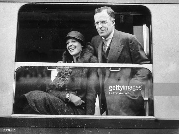 American aviator Amelia Earhart and her husband, publisher, George Palmer Putnam, laugh and looking out a window while traveling by train in...