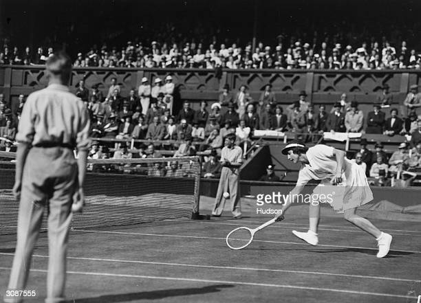 Helen WillsMoody reaching for a ball in her match against Peggy Scriven during the Wightman Cup at Wimbledon Lawn Tennis Club London Mrs WillsMoody...
