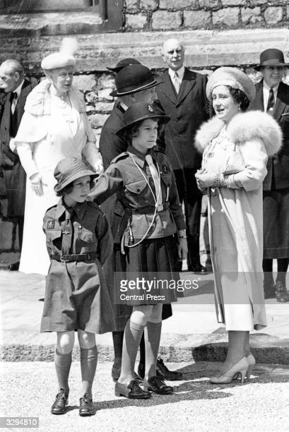 Princesses Elizabeth and Margaret Rose wearing Girl Guide costumes whilst Queen Mary and Queen Elizabeth Queen Consort to King George VI look on...