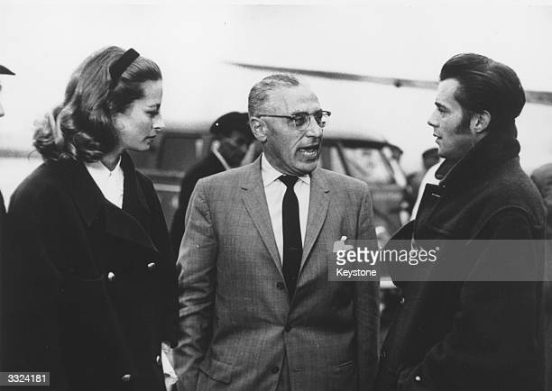 English actor and author Dirk Bogarde with the leading stars of the Hollywood film 'A Magic Flame', George Cukor and French actress Capucine at...