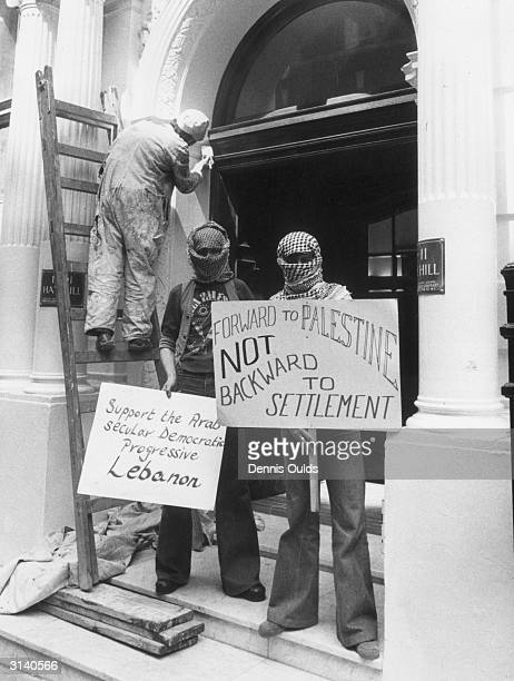 Two Arab students standing in front of an uninterested painter and decorator during a protest at the London offices of the Arab League against Syrian...