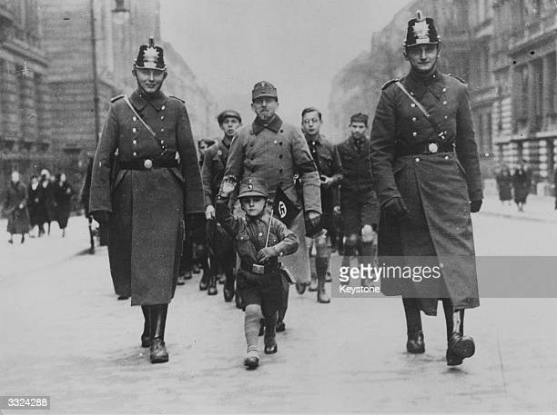 A tiny Nazi supporter escorted by two policeman heading a procession in celebration of the Nazi's victory in the general election