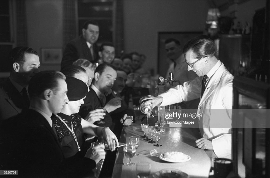 A barman pouring one of his special cocktails into four glasses during a Gastronomic Festival at the Grand Hotel in Torquay. Original Publication: Picture Post - 5220 - Cocktails For Four - pub.1951
