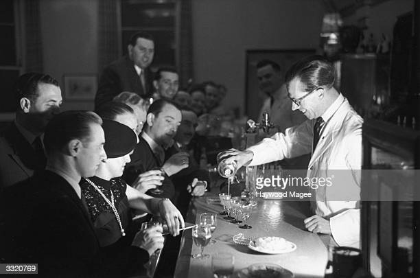 A barman pouring one of his special cocktails into four glasses during a Gastronomic Festival at the Grand Hotel in Torquay Original Publication...