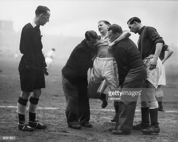 Blackpool player Stan Mortensen is carried from the pitch after a collision with Birmingham City goalkeeper Gil Merrick in the FA Cup semifinal at...