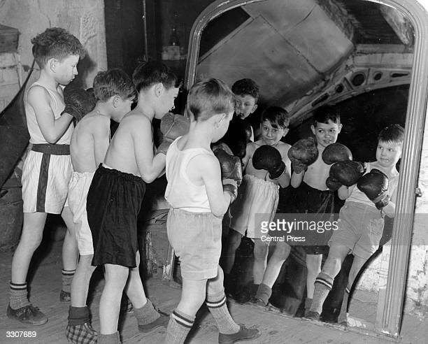 Four young boxers practice their shadow boxing in front of a large mirror at a Dundee gymnasium.