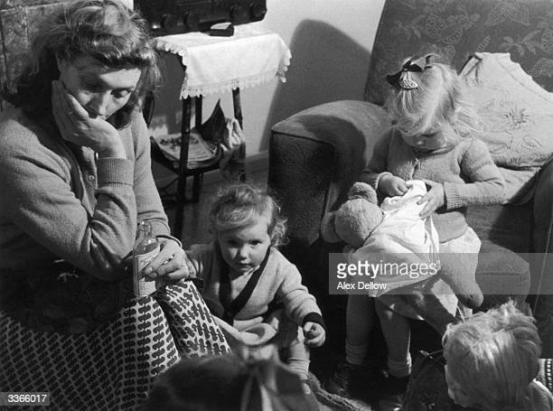 Housewife Annie Driver of Norfolk relaxes for a moment while looking after her children Original Publication Picture Post 8285 Motherhood The Job...