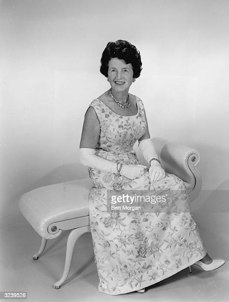 Full-length portrait of American political family matriarch and socialite Rose Kennedy seated wearing a floral gown and gloves.