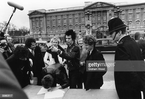 The Sex Pistols with their manager Malcolm McLaren signing a new contract with AM Records after being dropped from EMI outside Buckingham Palace...