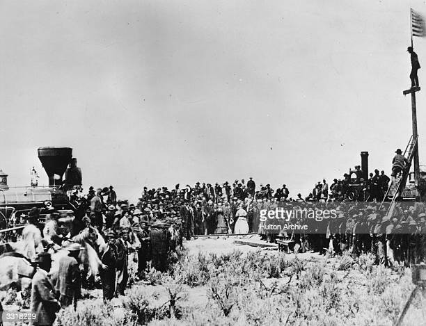 The golden spike is ceremonially driven in completing the first transcontinental railroad at Promontory Point Utah On the left is the Central Pacific...