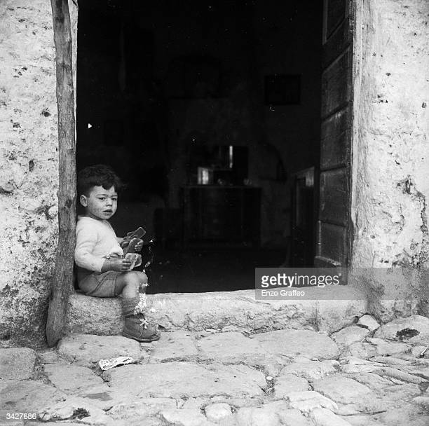 Young child plays on the doorstep of his home in Matera, near Naples. The houses in Matera are built on the crater of an extinct volcano. The Italian...