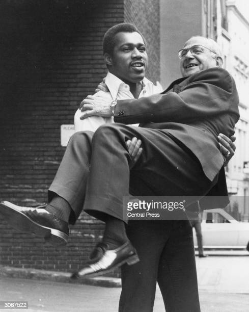 American heavyweight boxer Ken Norton gives a lift to boxing promoter Jack Solomons outside the Hertford Club where he is attending a reception given...