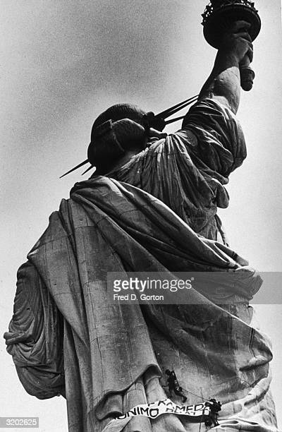 Political activists Edwin Drummond and Stephen Rutherford climb one third of the way up the back of the Statue of Liberty with a protest banner...