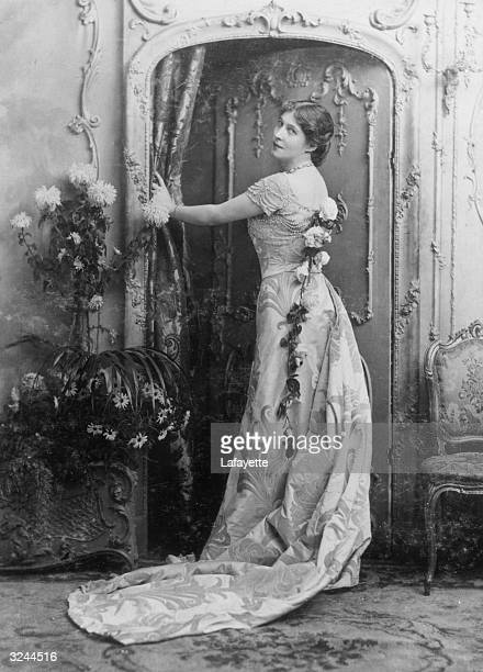 Fulllength portrait of English actress socialite and race horse owner Lillie Langtry wearing a gown fresh flowers cascading down her back standing by...