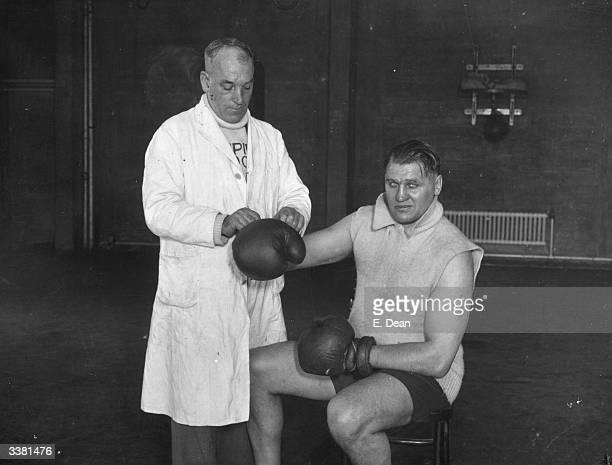 British Heavyweight Champion Phil Scott trainer lacesup his boxing gloves at the gymnasium at Wembley Stadium London