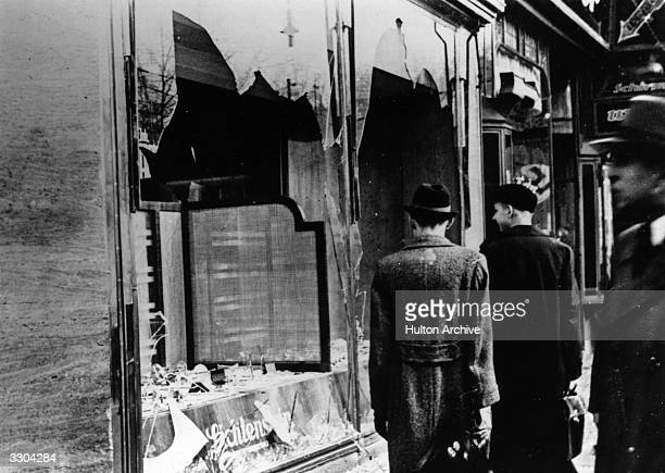 Three onlookers at a smashed Jewish shop window in Berlin following riots of the night of 9th November