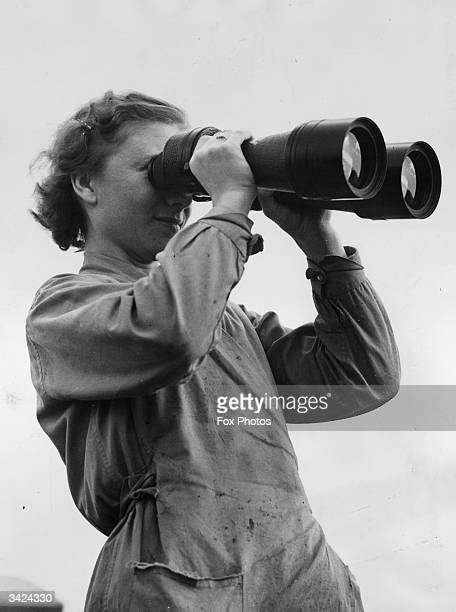A woman holding a pair of binoculars the largest size ever manufactured for the Navy