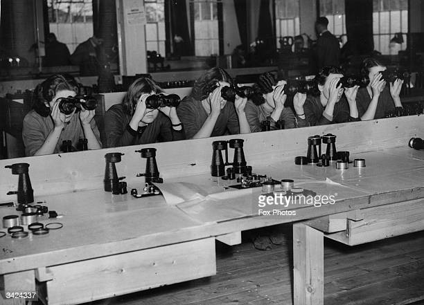 Workers in one of the largest optical instrument making factories in Britain, where binoculars, telescopes, photographic lenses and other scientific...