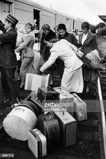 Travellers claim their luggage after it had been unloaded from a Royal train during a tour of Canada by Princess Elizabeth and Prince Philip Original...