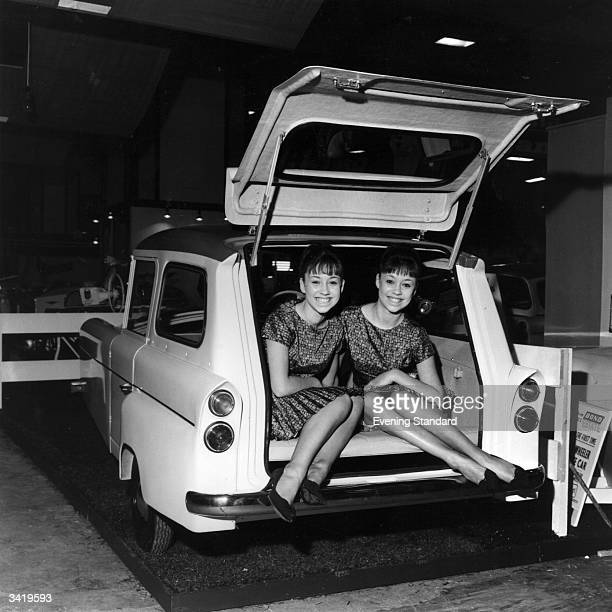 Janet and Jennifer Allman in a three-wheeled estate version of a Bond Minicar at the Motorcycle Show.