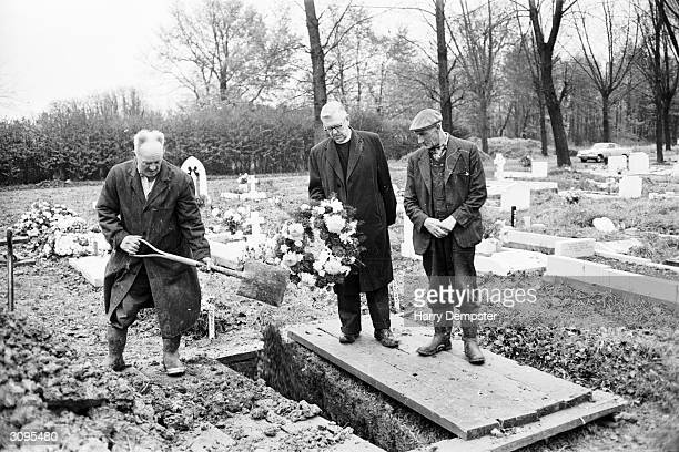 From left to right gravedigger Gledwin Frederick the Reverend Leslie Elliott and foreman Tom Worley prepare for the reburial of Timothy Evans at...
