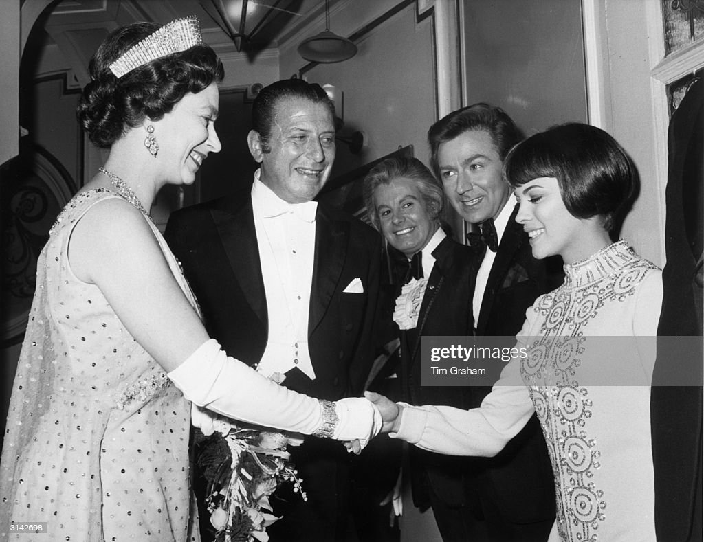 Queen Elizabeth II meets Mireille Mathieu during the aftershow presentation following the Royal Variety Performance, which had taken place at the London Palladium; also seen here are (left to right) Bernard Delfont, Danny La Rue and Des O'Connor.