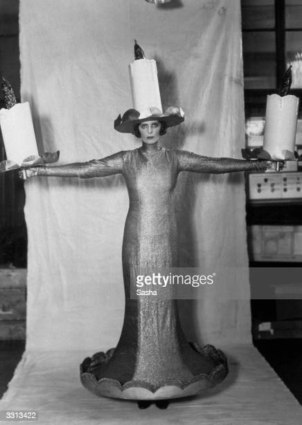 The Hon Mrs Roland Cubitt dressed as 'Three Candles' in a costume made by L H Nathan Ltd for the Pageant Of The Superstitions a feature of the 'All...