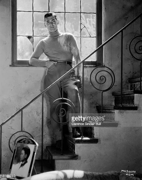 American actor Clark Gable poses halfway up a staircase in a pair of jodhpurs