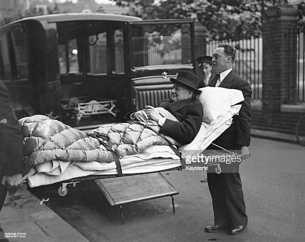 British statesman Winston Churchill is carried into his London home on a stretcher following his return from America where he was involved in a motor...
