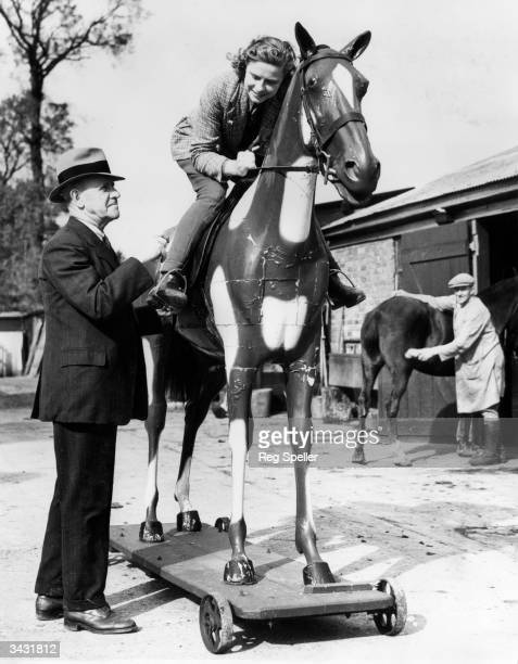 Miss I Croxton of Middlesex seated on a wooden horse is given training by her father in preparation for the Newmarket Town Plate The horse race for...