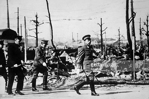 Emperor Hirohito of Japan on a tour of the devastated district of Tokyo after a raid by US bombers during the war in the Pacific