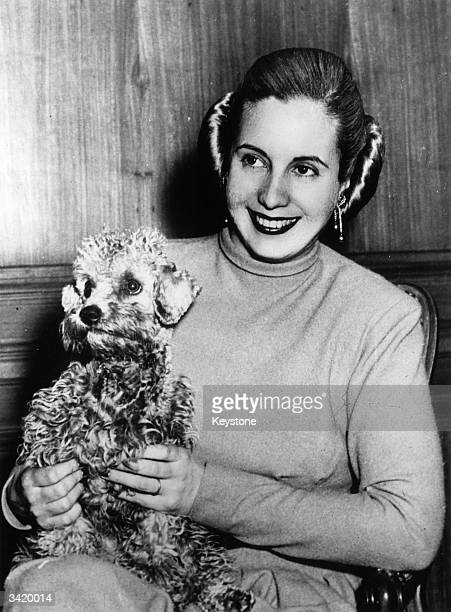 Former actress and wife of the Argentinian president Eva Duarte Peron popularly known as 'Evita' holding her pet dog at her home in Olivos a suburb...
