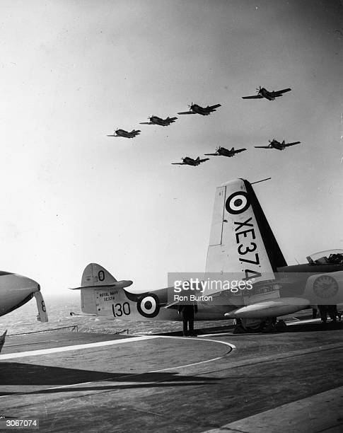 A squadron of Gannet antisubmarine aircraft fly over the HMS Ark Royal during the carrier drill and flying trials in the English Channel