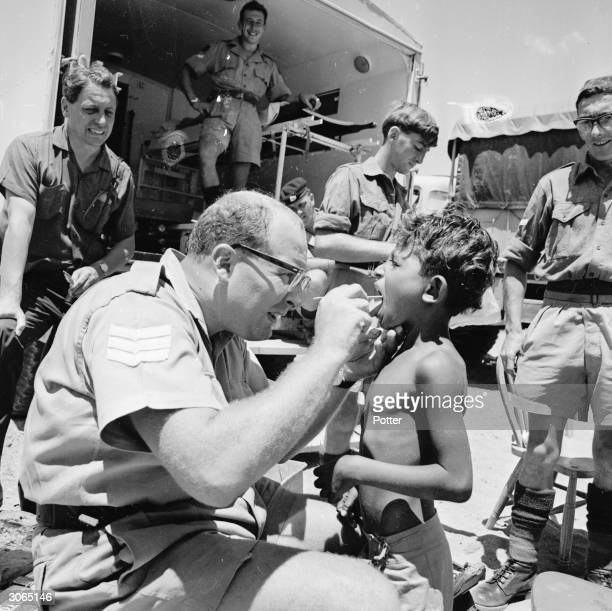Arab children queue up for medical attention from British serviceman Sergeant Tony Spargo in Aden