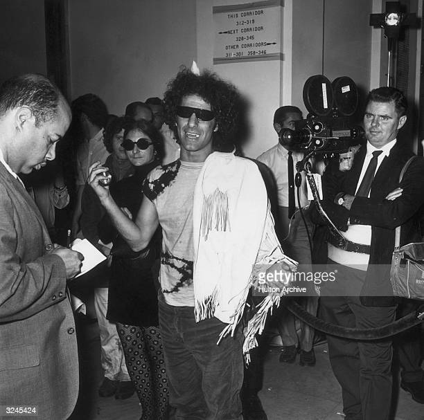 American political activist and Yippie founder Abbie Hoffman wearing dark sunglasses in a hallway before testifying for the House Committee on...